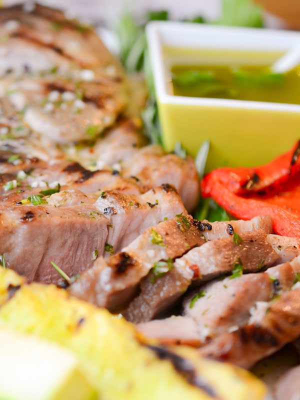 sliced pork steaks with grilled veggies and bowl of vinaigrette
