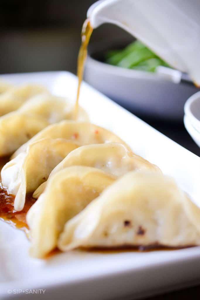 pouring dumpling sauce over gyoza