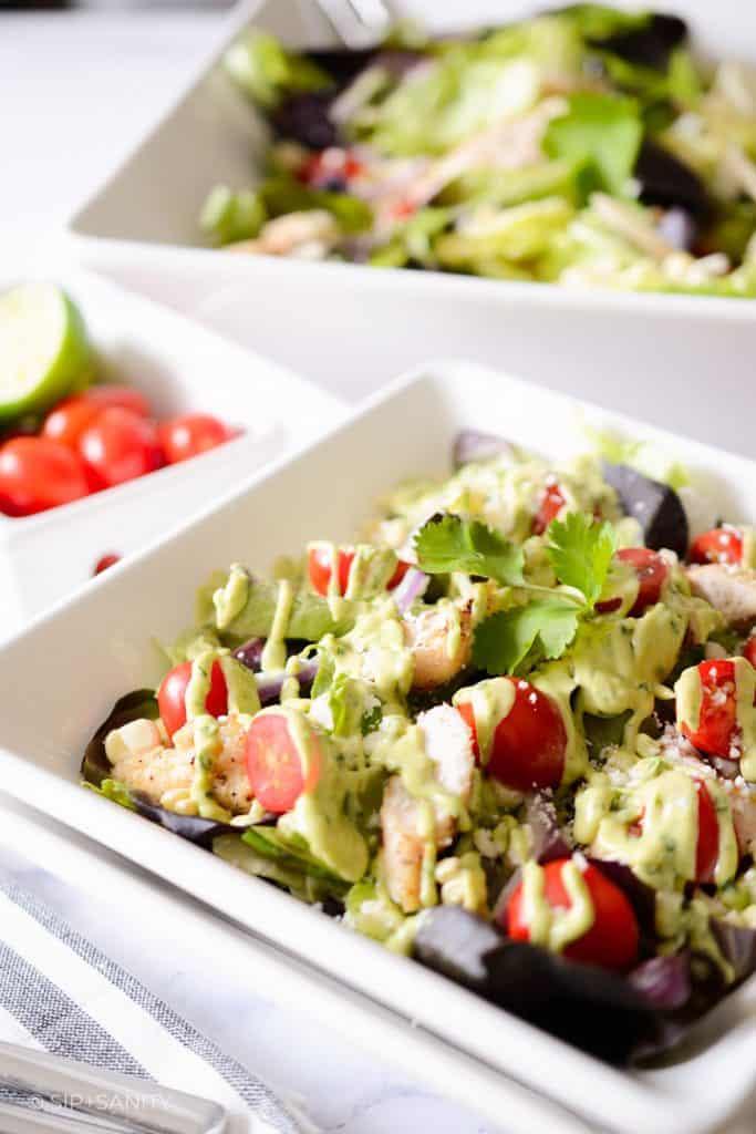 large bowl of salad behind a smaller bowl of salad