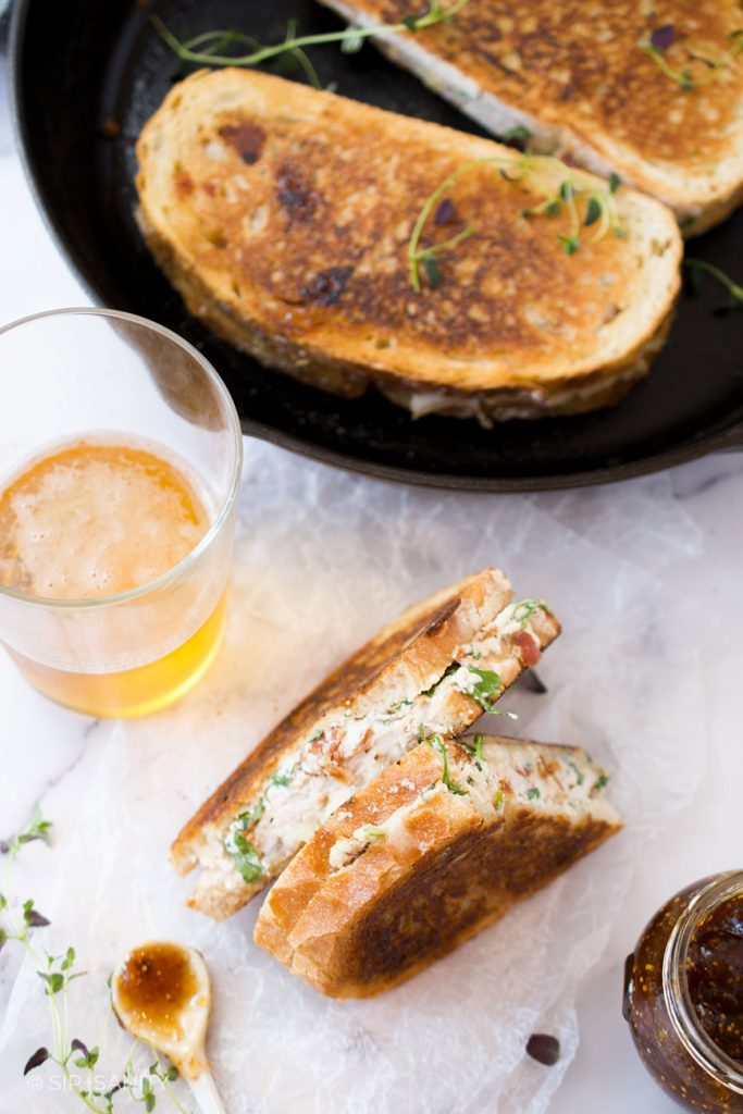 grilled cheese sandwich, a glass of beer and a skillet with sandwiches