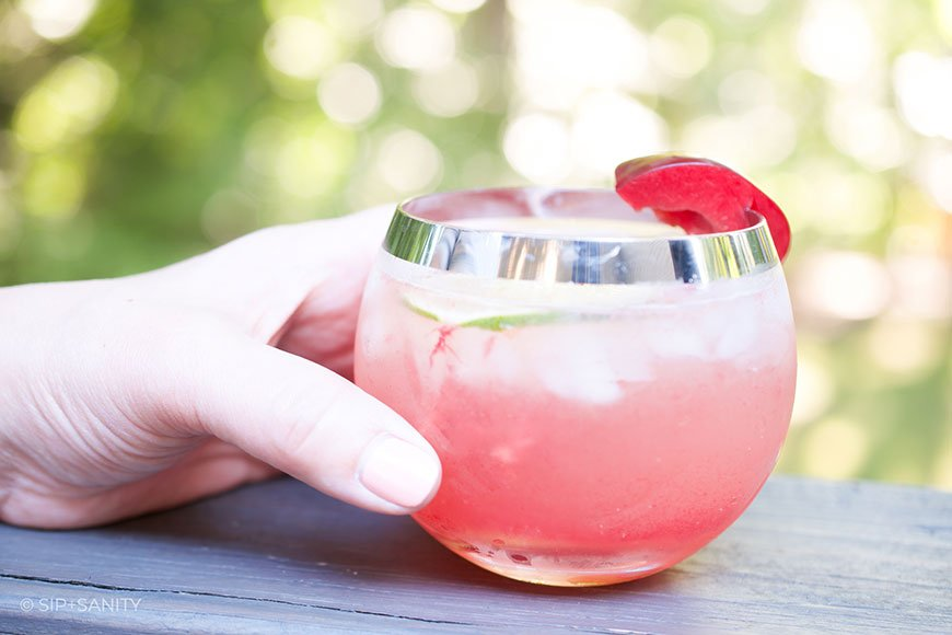 hand holding a glass of plum and lime whiskey smash