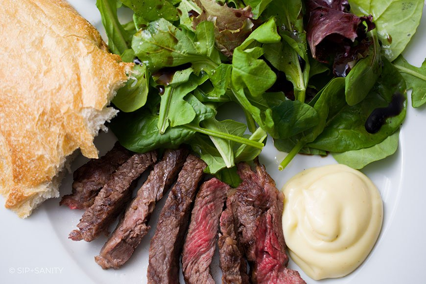 plate with french bread, salad, steak and mayo