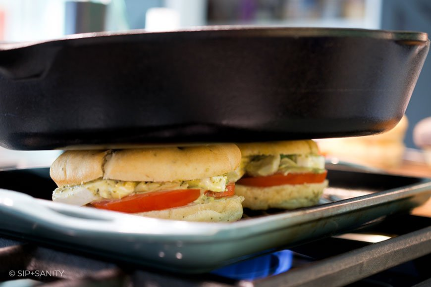 panini sandwiches being pressed by a cast iron skillet