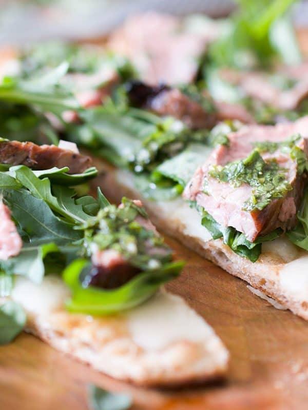 sliced flat bread with arugula, steak and chimichurri