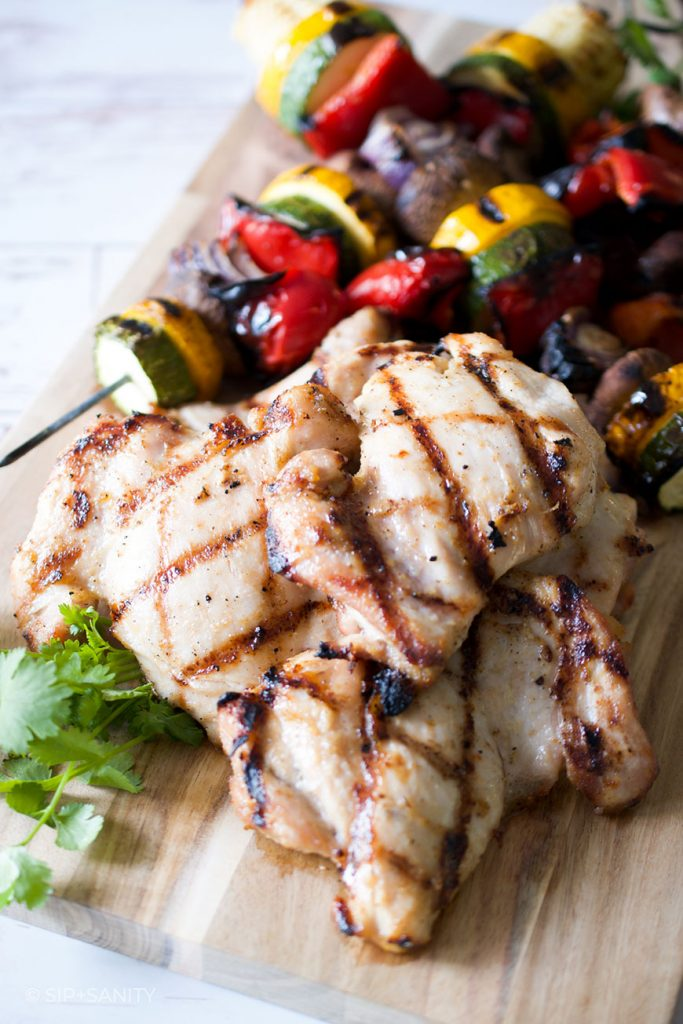 grilled chicken on cutting board with vegetable skewers