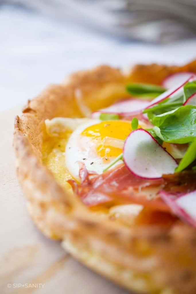 closeup photo of a fried egg, ham and salad atop a German Pancake