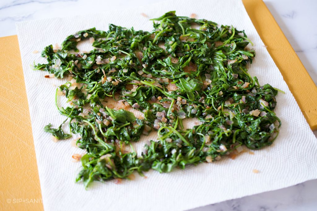 wilted arugula draining on a paper towel