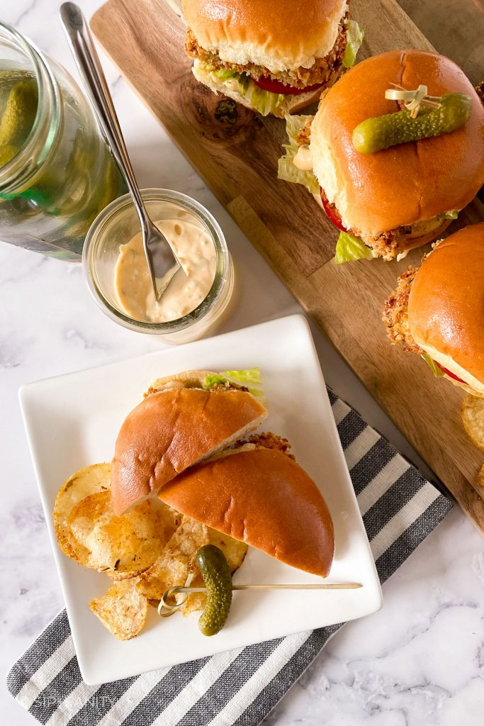 overhead image of a serving board of chicken sliders, and one a plate