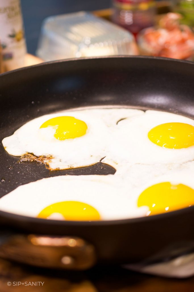 four fried eggs in a non-stick skillet