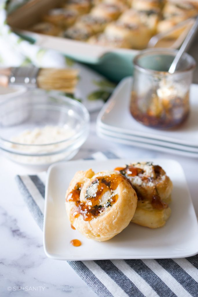 a table scene with pan of rolls, fig jam and two brunch rolls on a plate