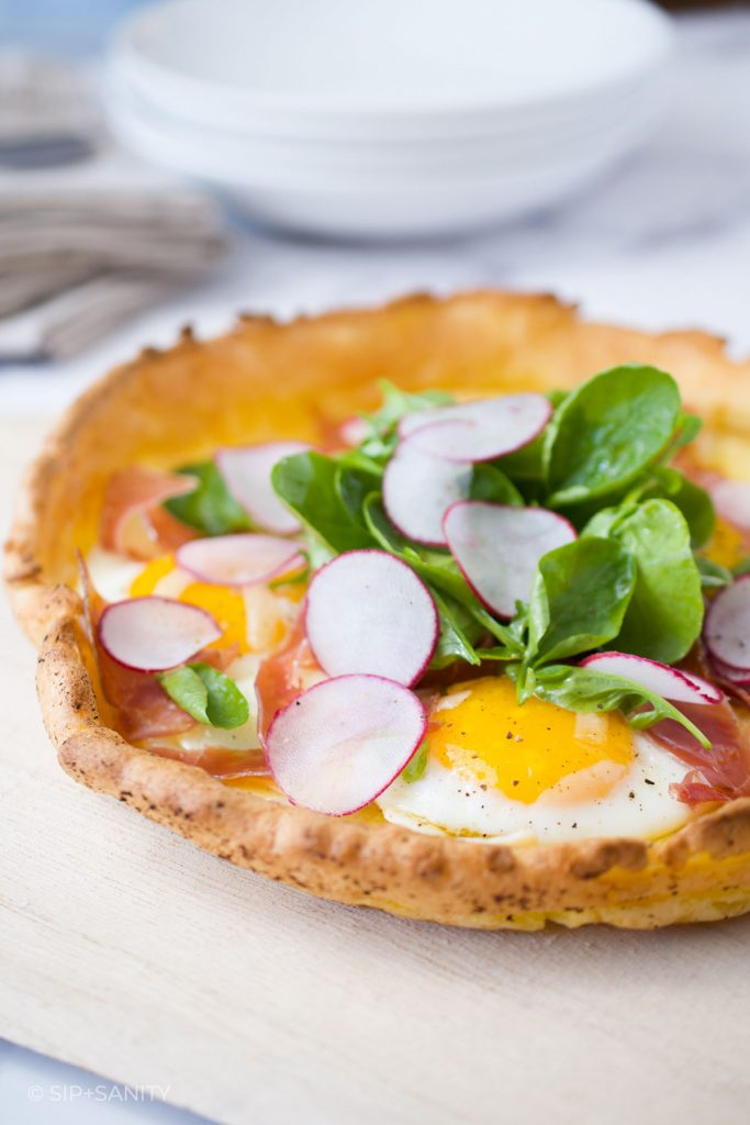 savory dutch baby with fried eggs, ham, cheese and salad greens