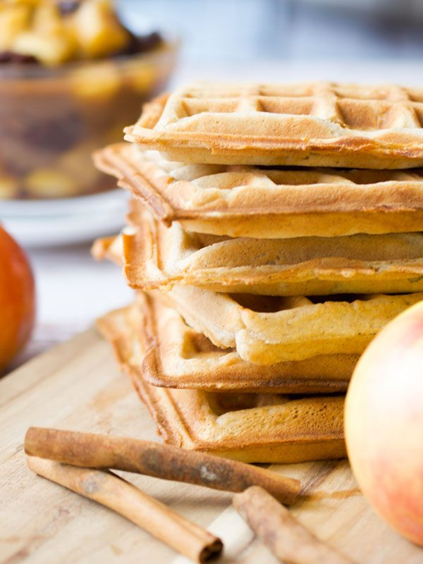 a stack of spiced apple waffles next to fresh whole apples