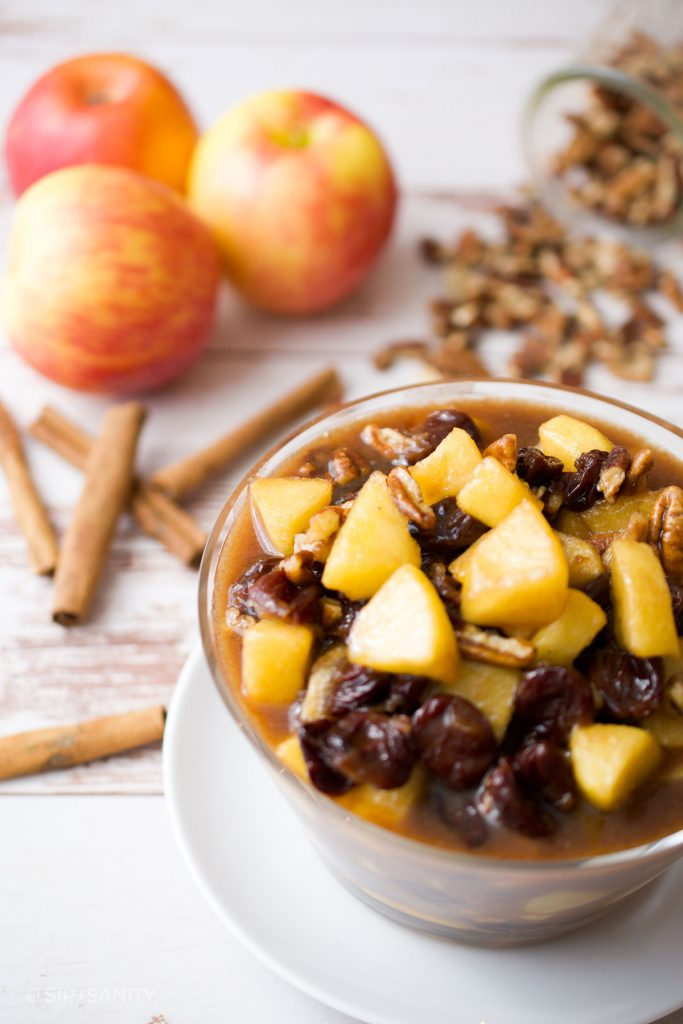 a bowl of caramel apple compote surrounded by apples, cinnamon sticks and nuts