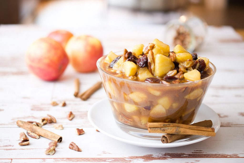 a bowl of caramel apple compote with apples, cinnamon and nuts in the background