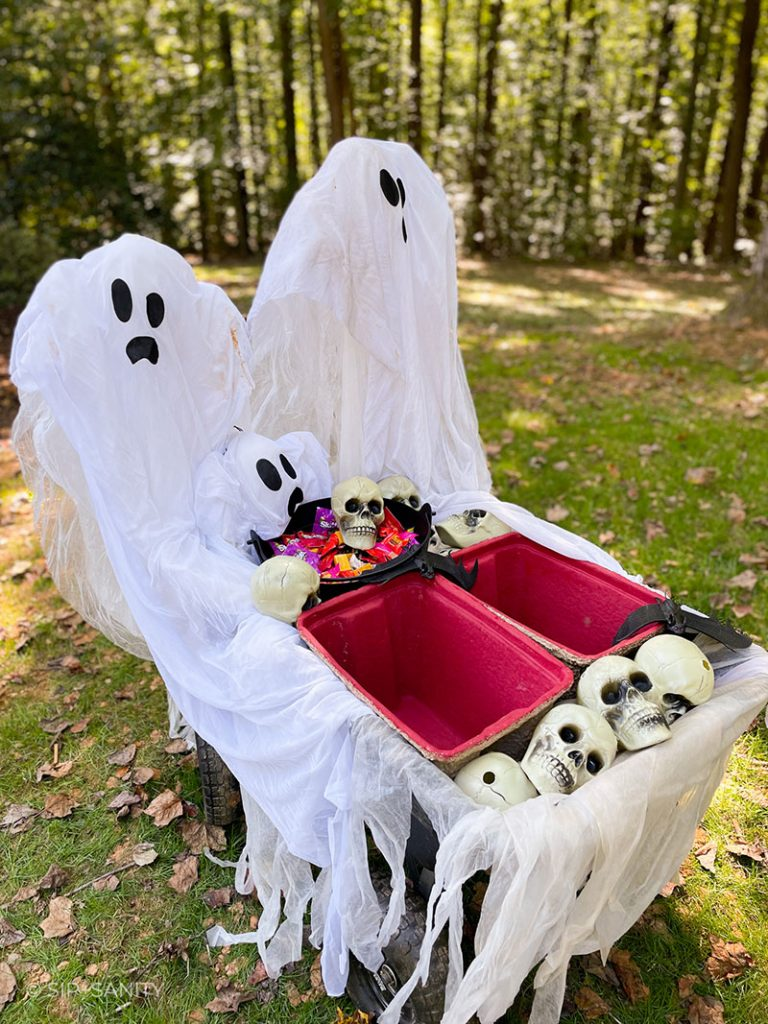 a completed halloween party on wheels with ghosts, candy, coolers and plastic skulls