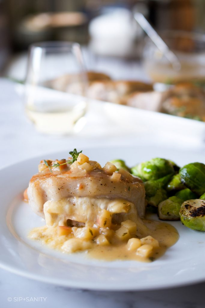 an apple and havarti stuffed pork chop with pan sauce and brussels sprouts