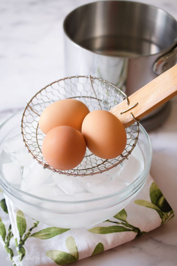 boiled eggs going into a bowl of ice water