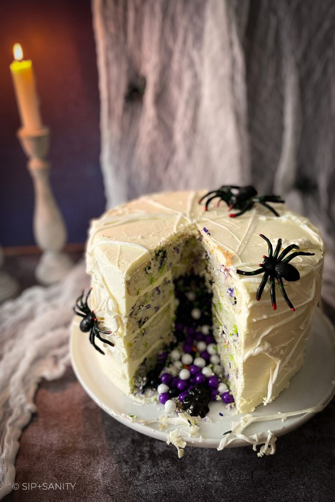 marshmallow spiderweb halloween cake with a slice cut out