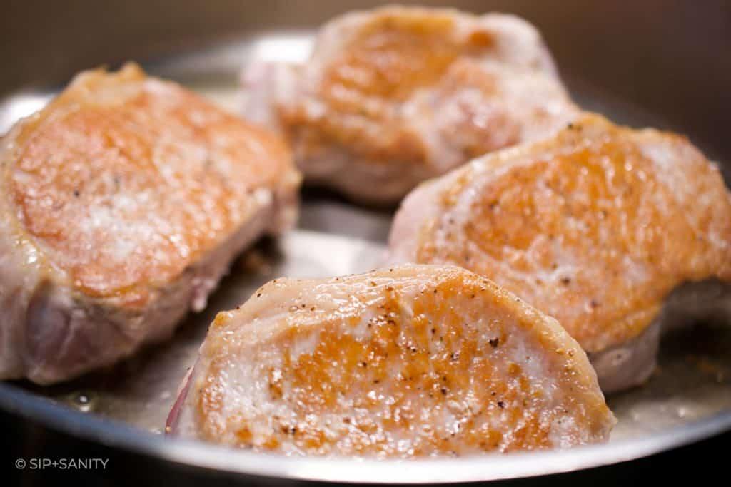 golden seared pork chops in a pan