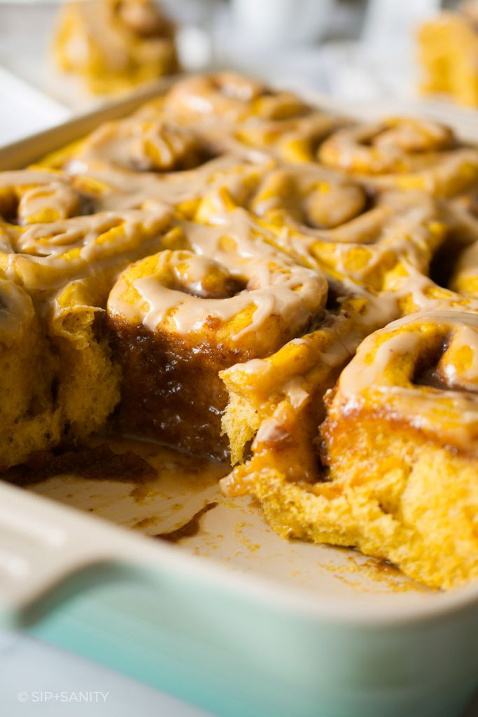 a pan of sweet rolls with a couple missing