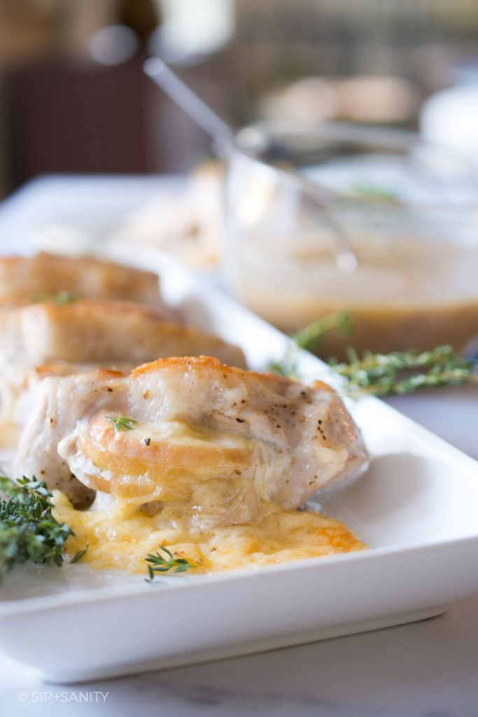 havarti and apple stuffed pork chops with a bowl of apple cider pan sauce