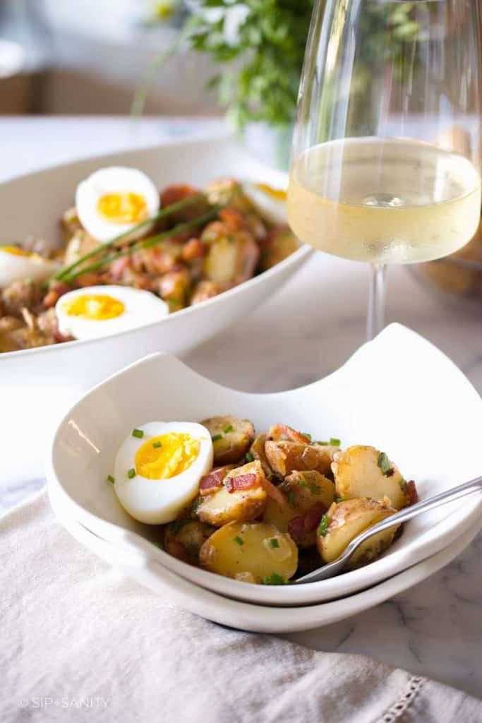 small bowl of potato salad next to a glass of white wine