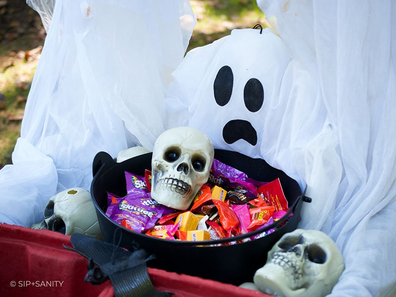 a ghost, a bowl of candy and some plastic skulls