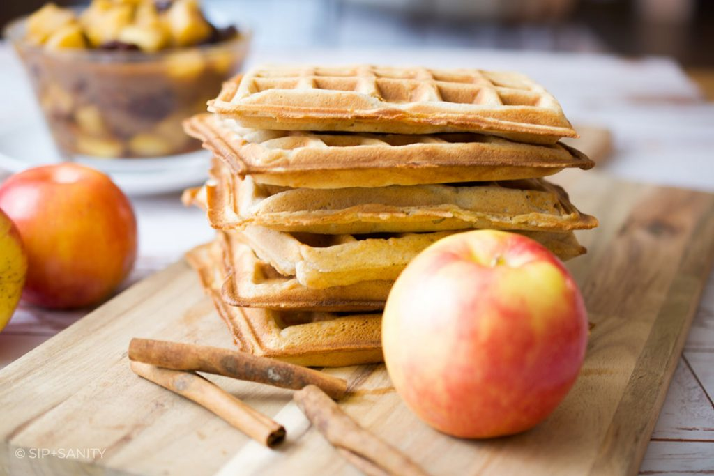 a stack of spiced apple waffles, some apples and cinnamon sticks