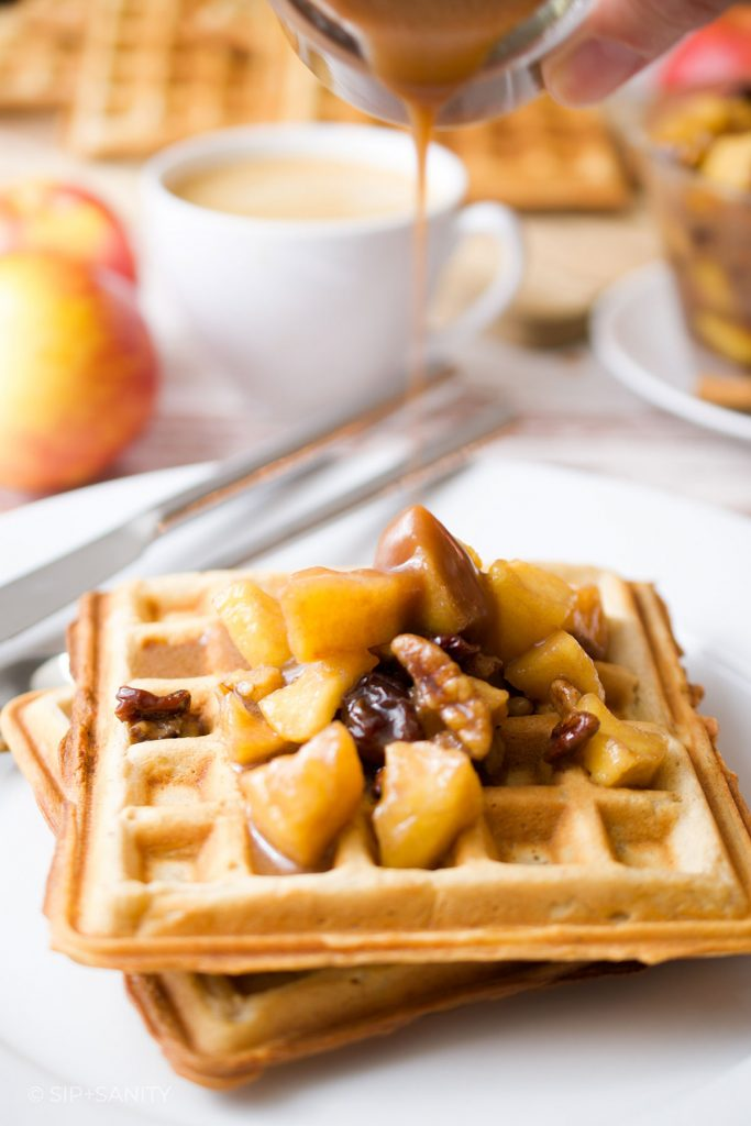 pouring caramel apple compote over spiced apple waffles