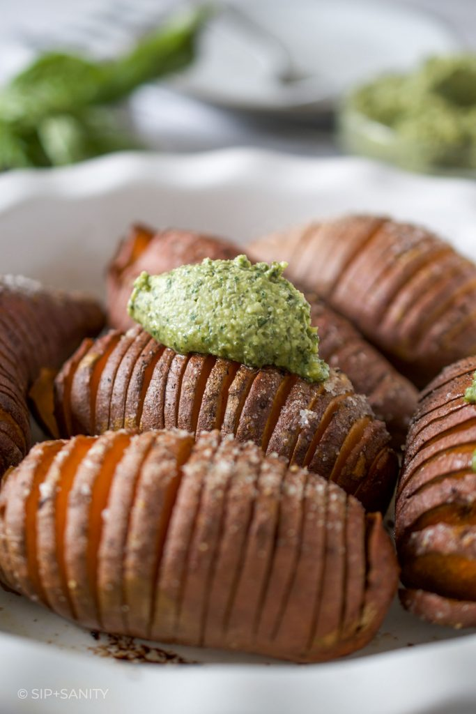roasted sweet potatoes in a pie plate and a dollop of pesto butter