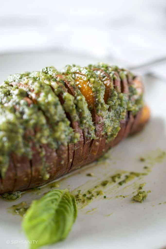 closeup of a hasselback sweet potato with pumpkin seed pesto butter