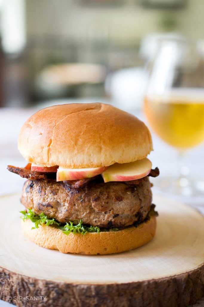 a fall harvest turkey burger with a glass of hard cider