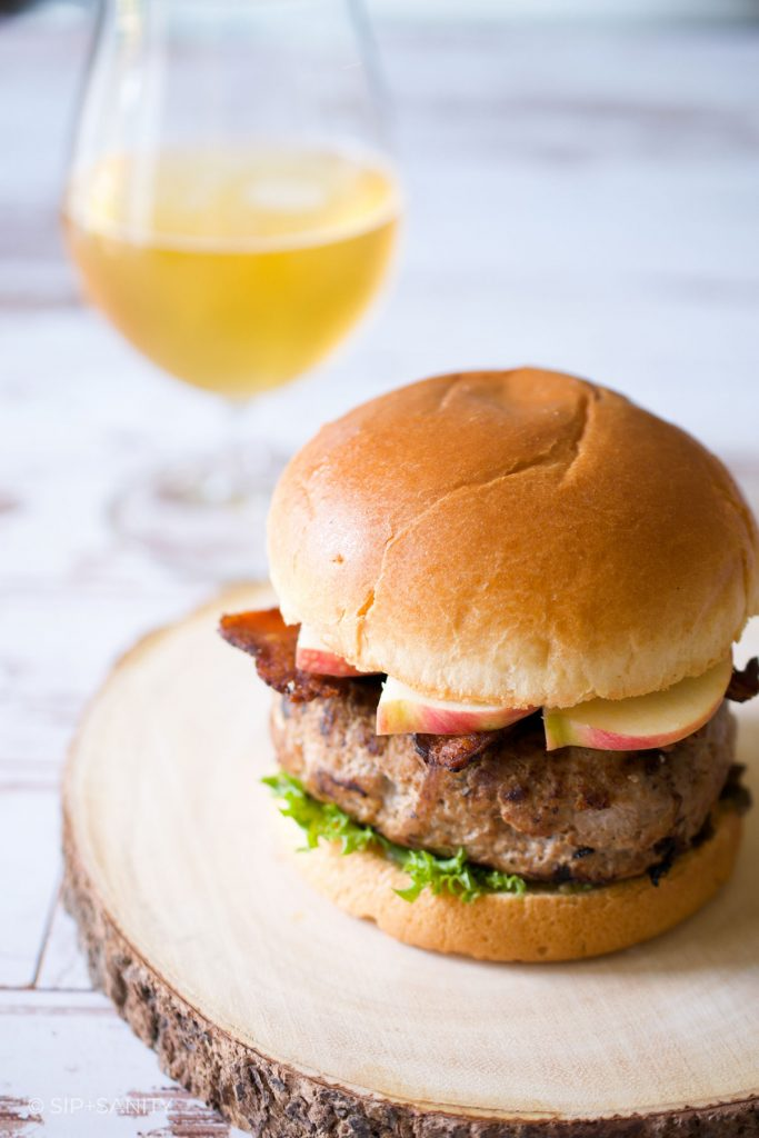 a fall harvest turkey burger next to a glass of cider