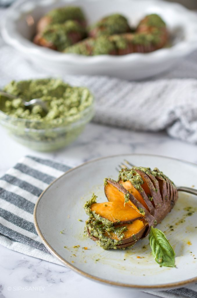 pie dish with roasted sweet potatoes, bowl of pumpkin seed pesto butter and single potato on a plate