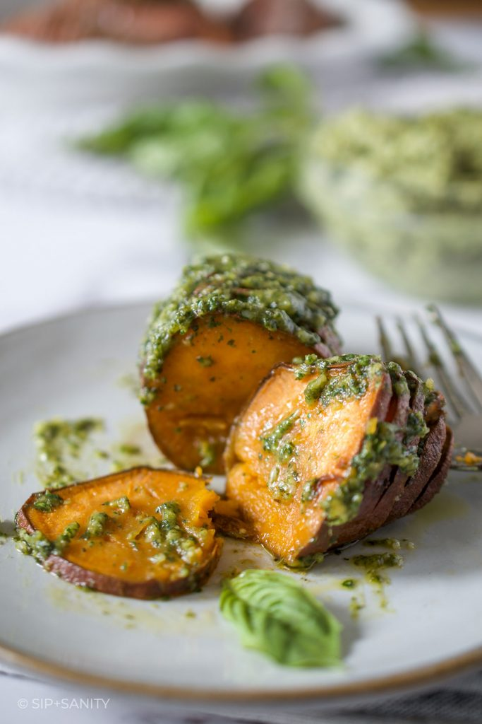 hasselback sweet potato with pesto butter on a plate