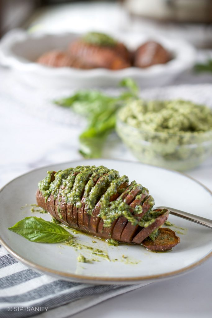 hasselback sweet potato with pumpkin seed pesto butter on a plate
