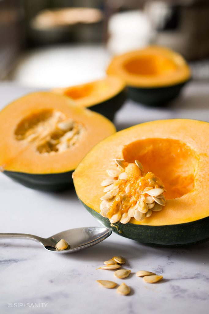 scooping seed out of acorn squash