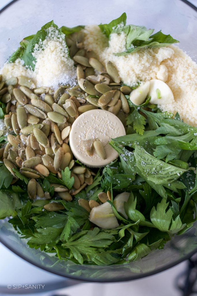 ingredients for pumpkin seed pesto butter in a food processor