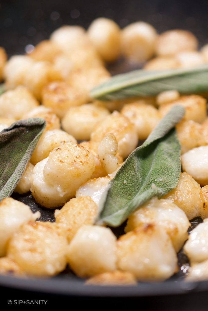 bay scallops and sage cooking in a skillet