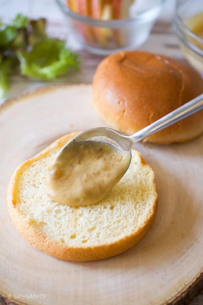 spreading dijonnaise on a toasted bun